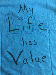 "Image description: the back of the same blue t-shirt with the words ""My life has value"""